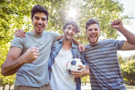 soccer: Amigos felices en el parque con el f�tbol en un d�a soleado Foto de archivo