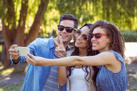 signo de paz: Amigos felices que toman una selfie en el parque en un día soleado