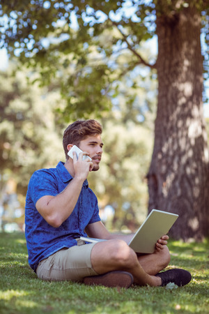summers: Hipster using laptop in the park on a summers day Stock Photo