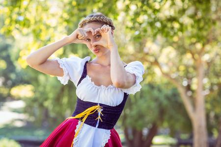 oktoberfest: Pretty oktoberfest blonde smiling in the park on a sunny day Stock Photo