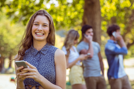 wireless connection: Happy friends in the park using their phones on a sunny day