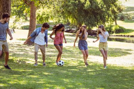 jugando al futbol: Amigos felices en el parque con el f�tbol en un d�a soleado Foto de archivo