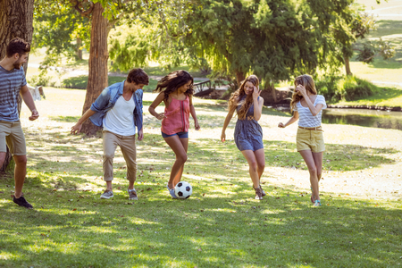 man long hair: Happy friends in the park with football on a sunny day Stock Photo