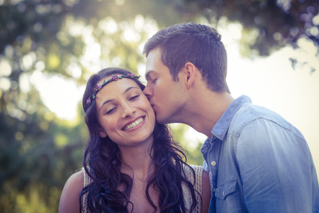 pareja besandose: Linda pareja bes�ndose en el parque en un d�a soleado