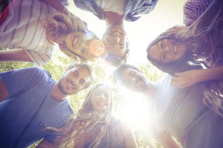 amabilidad: Amigos felices que amontonan en círculo en el parque en un día soleado