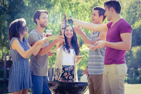 Glückliche Freunde, die im Park mit Grill an einem sonnigen Tag