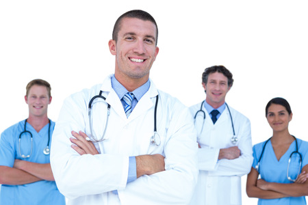 doctors smiling: Smiling doctors and nurses standing with arms crossed