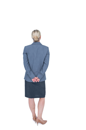 hands behind back: Businesswoman standing with hands behind back on white background