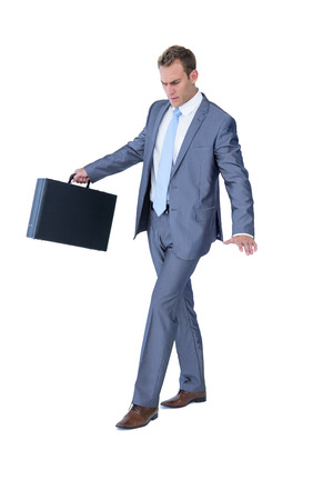 equilibrium: Businessman walking in equilibrium with suitcase on white background