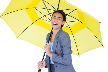sheltering: Smiling businesswoman sheltering under umbrella on white background