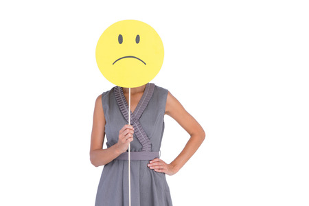 unhappiness: Businesswoman holding sad smiley face on white background