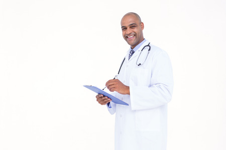 tunic: Confident doctor in white tunic writing notes on a notebook Stock Photo