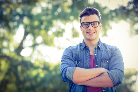 young man smiling: Happy hipster looking at camera on a sunny day