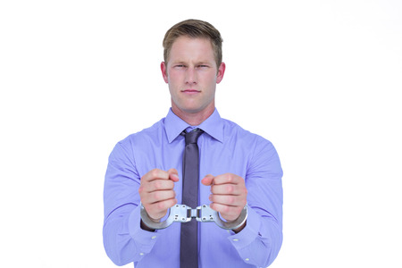 restraining device: Handsome businessman wearing handcuffs on a white background Stock Photo