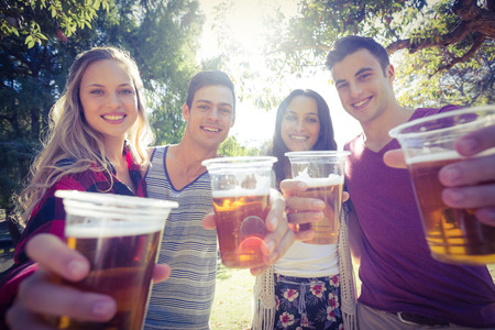 weekend activity: Happy friends in the park having beers on a sunny day