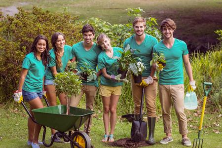 Pflanzen: Glückliche Freunde, die Gartenarbeit für die Gemeinschaft an einem sonnigen Tag