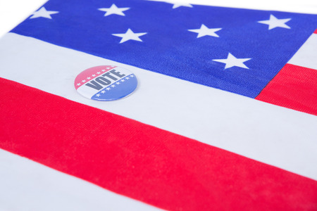 election choices: Badge put on American flag on white background