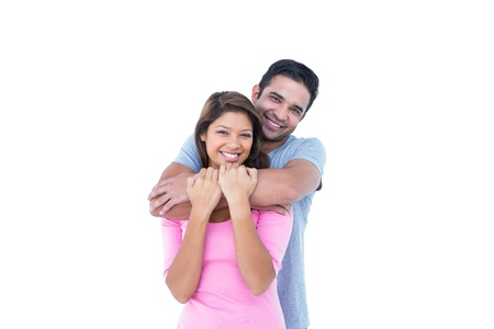 Happy couple embracing and looking at the camera on white background Foto de archivo