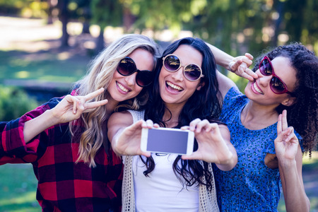 friendships: Happy hipsters taking a selfie in the park on a sunny day