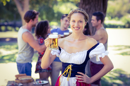 oktoberfest: Pretty oktoberfest blonde toasting in the park on a sunny day