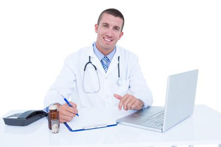 medecine: Smiling doctor writing on a notebook