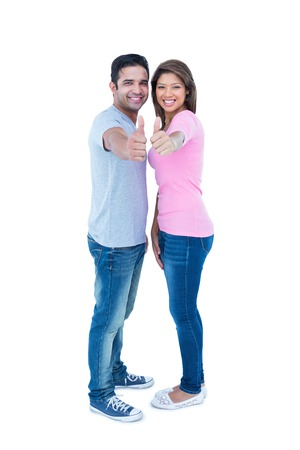 Happy couple gesturing thumbs up and looking at camera on white background Stock Photo