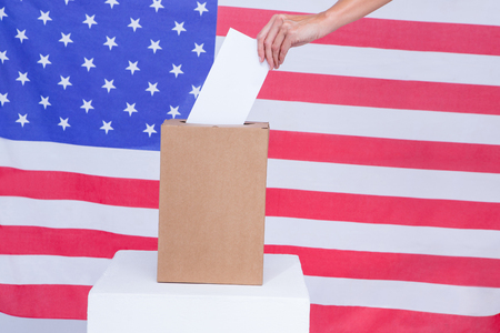 election choices: Composite image of hand putting ballot in vote box behind american flag Stock Photo