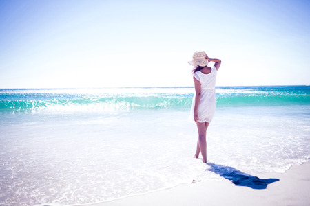 freedom woman: Pretty brunette wearing straw hat and walking in the water at the beach