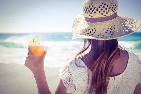sol radiante: Brunette con el sombrero de paja y la celebración de un cóctel en la playa