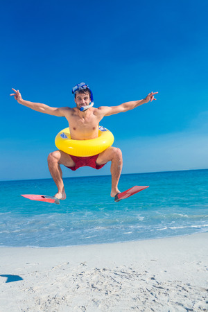 rubber ring: Man wearing flippers and rubber ring at the beach on a sunny day