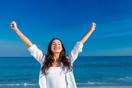 Happy woman smiling at the beach on a sunny day Stockfoto