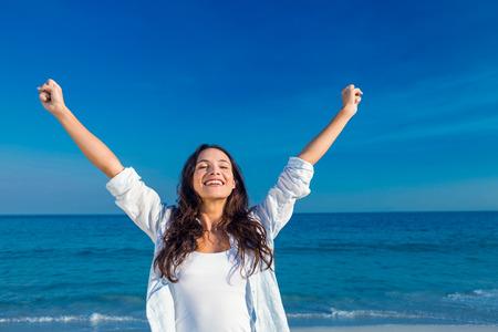 Gelukkige vrouw lachend op het strand op een zonnige dag Stockfoto