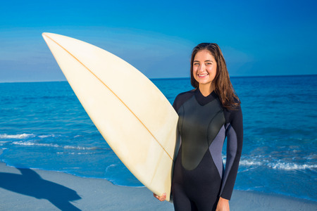 wetsuit: Woman in wetsuit with a surfboard on a sunny day looking at camera