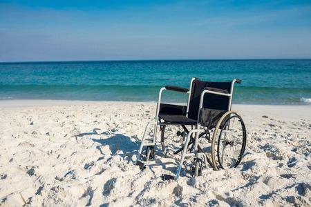 paraplegic: Silla de ruedas Negro en la playa Foto de archivo