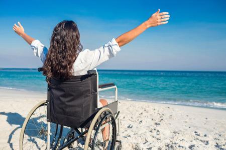 paraplegico: Mujer lisiada con los brazos extendidos en la playa en un día soleado Foto de archivo