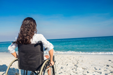 Disabled woman looking at the ocean on a sunny day Stock Photo
