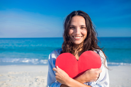 Smiling woman holding heart card at the beach on a sunny day Standard-Bild