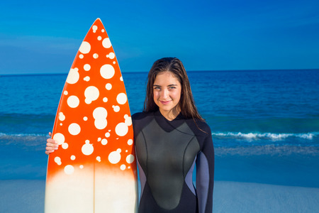 escapism: Woman in wetsuit with a surfboard on a sunny day looking at camera