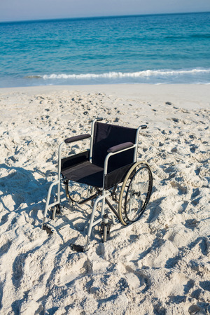 paraplegico: Silla de ruedas Negro en la playa Foto de archivo