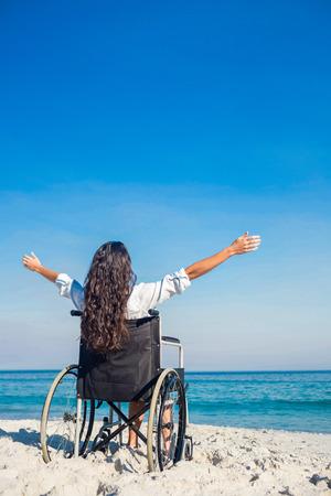 paraplegico: Mujer lisiada con los brazos extendidos en la playa en un d�a soleado Foto de archivo