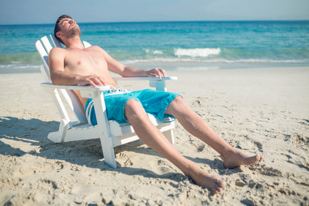 asleep chair: Man relaxing on deck chair at the beach on a sunny day