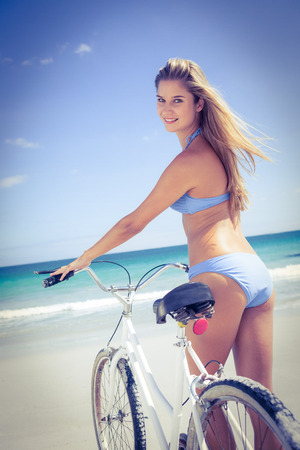 sexual activities: Pretty blonde woman going on a bike ride at the beach Stock Photo
