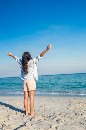escapism: Happy woman with arms outstretched at the beach on a sunny day Stock Photo