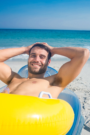 escapism: Handsome man lying on the beach looking at camera on a sunny day Stock Photo