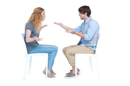 argumento: Pareja sentada teniendo una discusión en el fondo blanco Foto de archivo