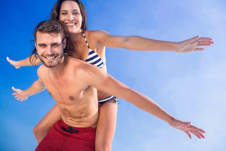 couple  amoureux: Homme donnant piggy back � sa petite amie � la plage sur une journ�e ensoleill�e