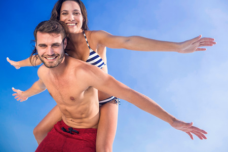 love couple: Man giving piggy back to his girlfriend at the beach on a sunny day Stock Photo
