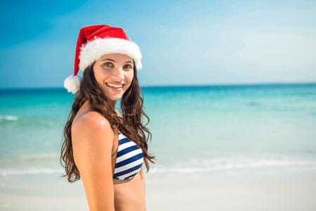 summer vacation bikini: Pretty brunette in santa hat looking at camera at the beach