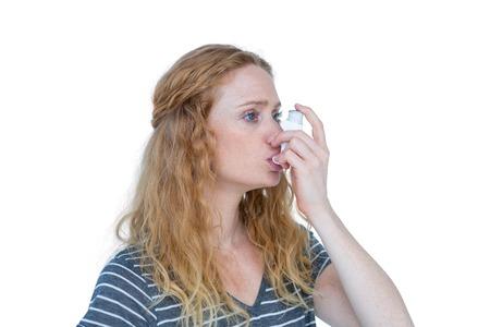 inhaler: Pretty blonde using an asthma inhaler on white bakcground