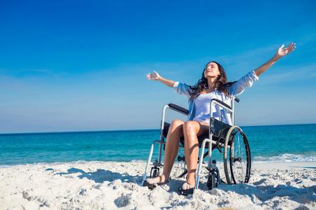 persona en silla de ruedas: Mujer lisiada con los brazos extendidos en la playa en un d�a soleado Foto de archivo